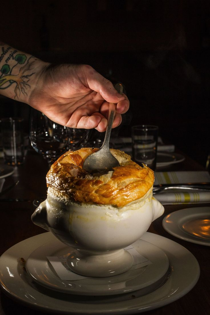 L'Oursin's fish soup en croute has a bulbous golden crust that shelters a trove of shellfish and finfish awash in saffron-scented seafood stock. (Dean Rutz/The Seattle Times)