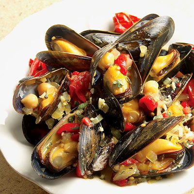Recipe for Spanish Tapas Inspired Mussels - Shellfish, such as oysters and mussels, are thought to be some of nature's most powerful aphrodisiacs. In this dish, dark mussel shells provide a striking contrast to the tomatoes, onions, garlic, and fragrant saffron that come together with dry sherry to create a flavorful sauce. Warm crusty French bread in the oven to soak up some of this dish's sauce