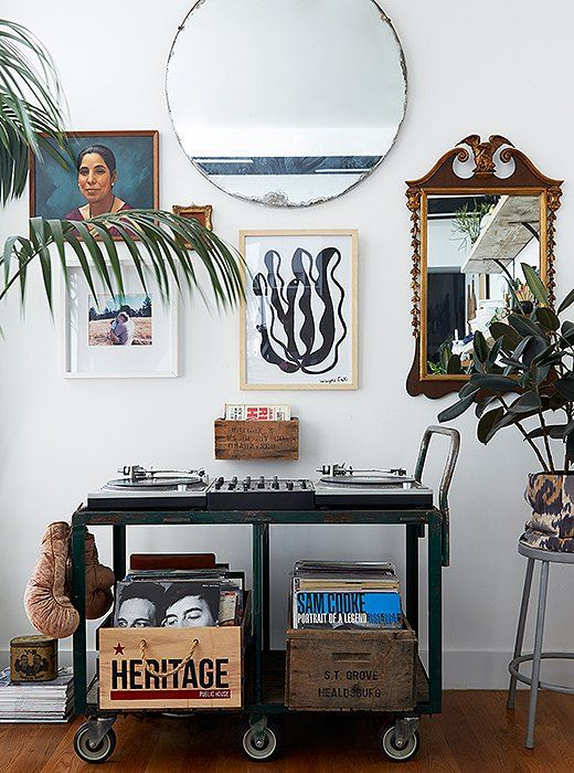 """I have two turntables, a mixer, speakers, and records,"" Rosie says. ""It can take up space and be a bit of an eyesore."" But she found an attractive solution in the form of her dad's old tool cart. And she created a chic gallery wall above the cart with a mix of mirrors and art."