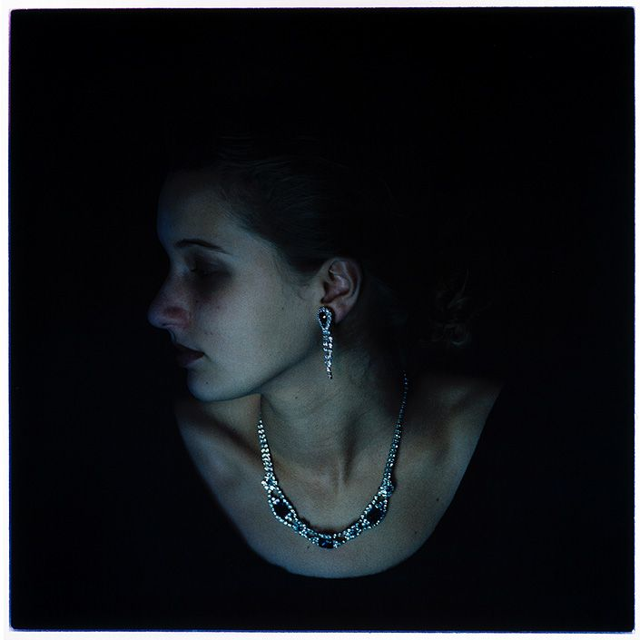 Bill Henson. Having a lot of solid black negative space around the subject is a good way to make them stand out. I like the cool tones used and how only her skin and jewellery are highlighted.