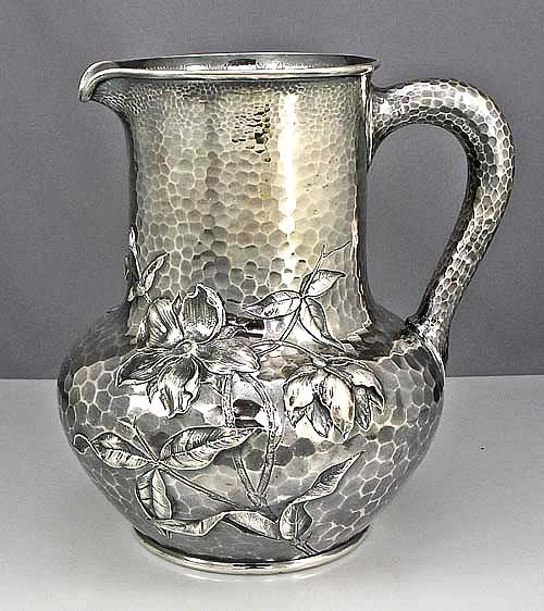 Caldwell Aesthetic Sterling Pitcher  Silver hand hammered water pitcher chased with flowers and leaves in the Japanese taste.