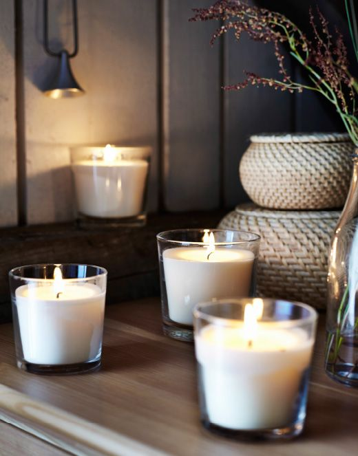 Nahaufnahme einiger brennender SINNLIG Duftkerzen im Glas Vanille/naturfarben