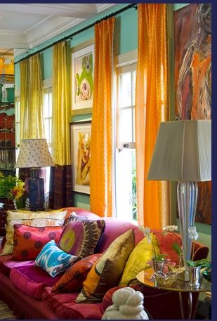 Love using two colors of drapes and the single track use. Also the picture stacking. Contemporary Art,bright colored throw pillows, this room has it all. Most importantly, the lamps are the right scale
