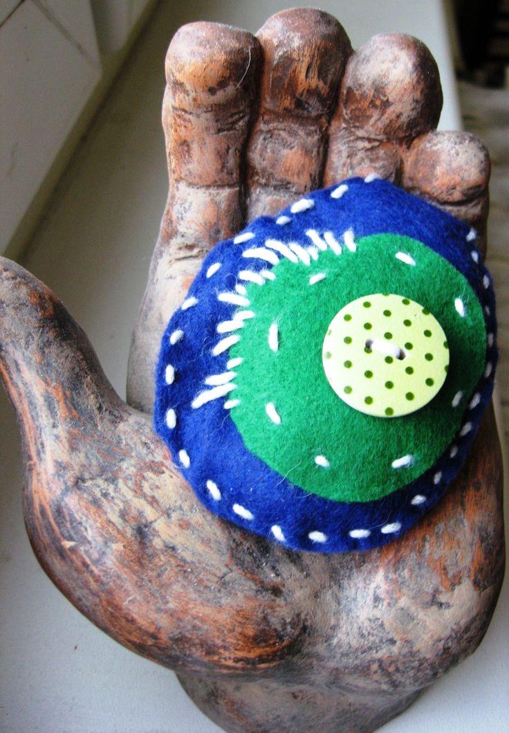 ...i kapkou rosy chtěl bych být... Brožka šitá z modrého a zeleného filcu s brožovým můstkem a dřevěným zeleným puntíkovaným knoflíkem, plněná vatelínem. Průměr vnějšího okraje 8 x 6,5 cm.