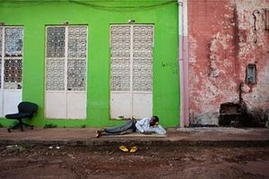 FTA: Joe Penney: A security guard relaxes in front of colonial-era buildings in Bissau