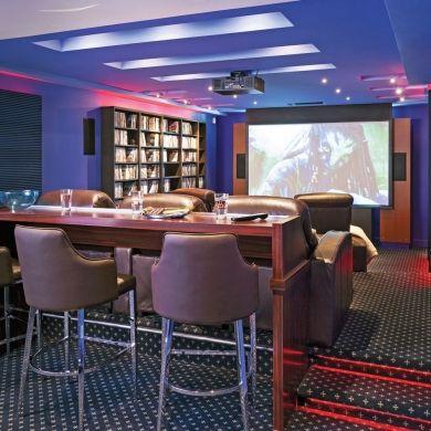 Fanas de cinéma, les proprios ont créé leur salle obscure dans les règles de l'art afin d'en optimiser la qualité acoustique et visuelle: haut-parleurs et caissons subwoofers intégrés dans les murs, écran géant avec projecteur, peinture matte pour éviter les reflets, lumières DEL à faible intensité et modulables selon l'ambiance désirée. Celles-ci ajoutent un climat magique au sous-sol. Posés sous les fauteuils, sous les comptoirs du bar ou sous les étagères, les éclairages...