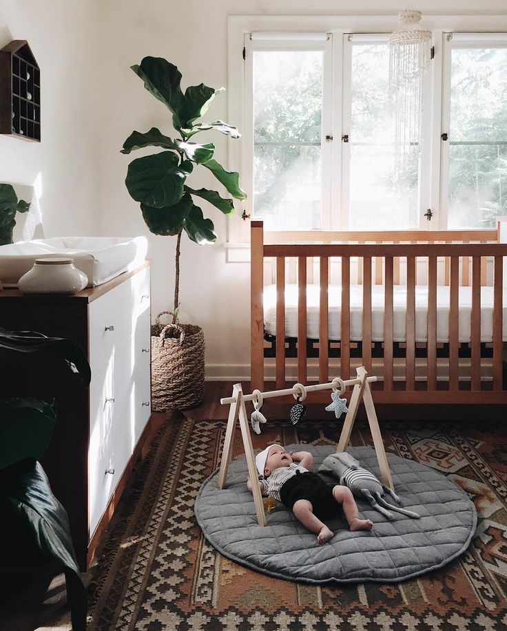 A warm modern nursery with wood, fiddled fig and other cozy elements