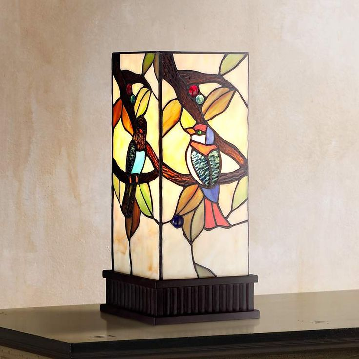 a colorful accent table lamp featuring a different tropical bird design on each panel