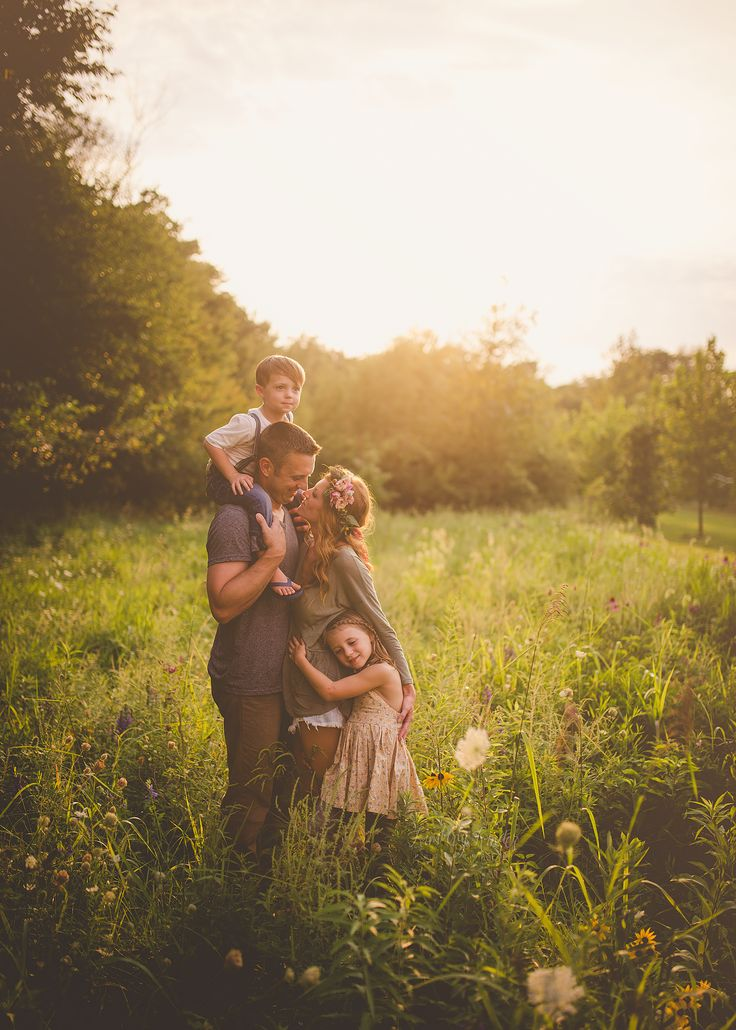 Beautiful family portrait in a wild field. The posing shows such sweet joy and the evening light has a warm glow.