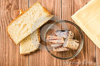 Canned fish. Sardine in oil. White bread. Wooden background. Top view