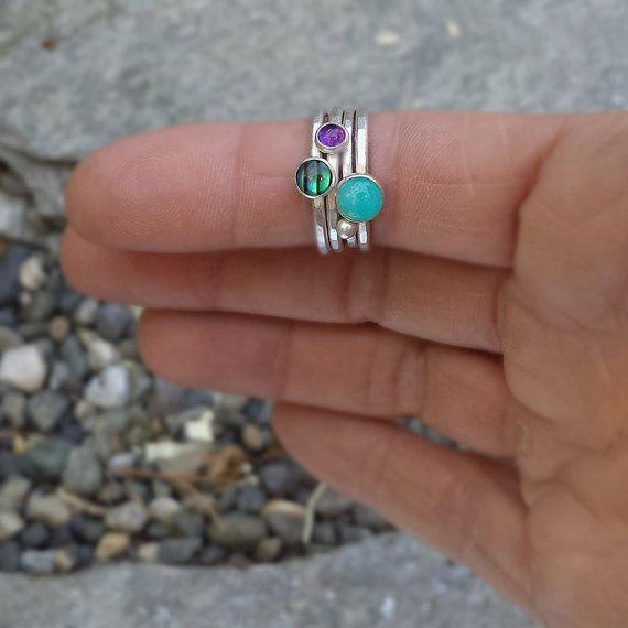 Een mooie set van vier stapelbare ringen in juweel tonen--Amazoniet, Paua (abalone) shell en paarse Amethist. Voltooiing van de reeks van vier ringen is een spacer band met een fijne zilveren stip. De ring-bands zijn gemaakt van gerecycled zilver, gegeven een geciseleerde textuur en vervolgens gepolijst.  DETAILS: -6mm Amazoniet cabochon op een ~ 2mm gehamerd sterling band; -5mm Paua cabochon, ~ 2mm gehamerd sterling band; -4mm paarse Amethist, ~ 2mm gehamerd zilver band; -een fijne zilveren…