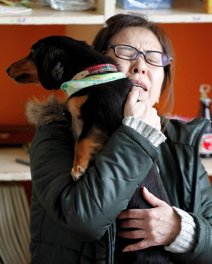 A woman comforts her dog during an aftershock at an evacuation center for pets and their owners in Japan.