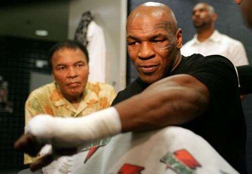 Muhammad Ali sits with Mike Tyson as he gets his hand wrapped before his fight with Kevin McBride on June 11, 2005 in Washington, D.C. In what would be his final professional fight, Tyson lost to McBride by TKO in the 6th round, finishing his career 50-6 with 44 wins by knockout. The former world heavyweight champion turned 49 years old today. (Neil Leifer for SI)