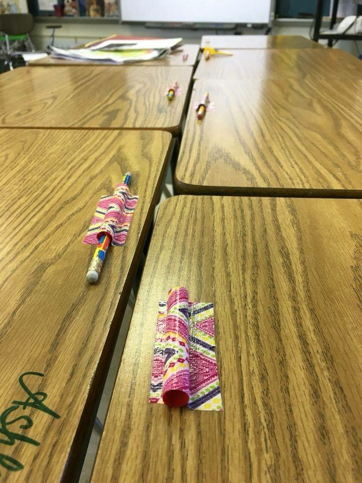 Cut straws and tape them to the desks. Slide the pencils in and voila! No more pencils falling off the desk and they are always handy.
