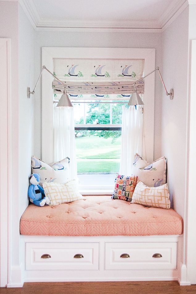 Happy little window seat in an historic home featuring tufted window seat cushion and pillows with angled arm sconces and a roman shade www.pencilshavingsstudio.com
