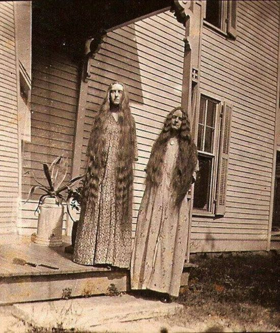 Creepy Old Vintage Photos~ two scary sisters with waist long hair standing on porch.  The stuff of nightmares.