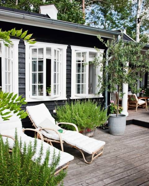 ah, the patio...or deck. love the open windows, white chairs and the galvanized pot for the plant.