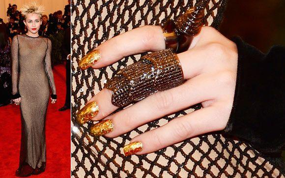 Miley Cyrus ficou glam com unhas douradas! Para copiar esse efeito tem que ter paciência: escolha um esmalte dourado como base e glitter balls bem concentrados do mesmo tom; então, aplique uma camada generosa do produto e extrabrilho por cima, para tudo ficar bem juntinho.