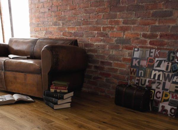 Déco indus avec mur en brique et vieux canapé/fauteuil club en cuir marron…