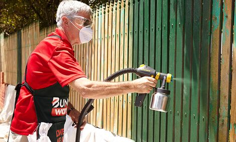 Man painting a timber fence green using a spray gun