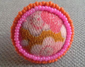 Textil del anillo Bobo, Ethno Chic, colores dinámicos, yesos rojos. Esta joya se llevó a cabo en un círculo de fieltro cubierto con fragmentos de saris indios cosido y bordado a mano. La Ronda está adornada con dos hijos de granos rojos. Anillo en rosa y rojo arroja Un hilo de pequeñas perlas de plata identifica el conjunto del anillo. Un botón antiguo con forma de bola de plata toma su lugar en el centro del tablero. Diámetro de la placa: 2, 7cm Plata ajustable sin anillo de metal nikel.