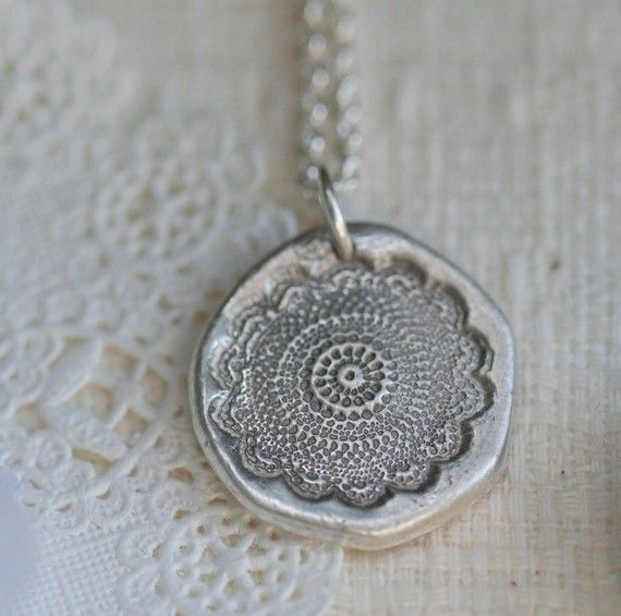 take clay, imprint some pretty charm (old buttons?) onto it, paint silver
