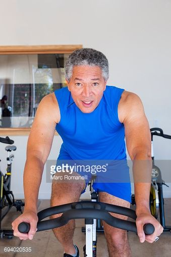 Stock Photo : Mixed Race man riding stationary bicycle in gymnasium