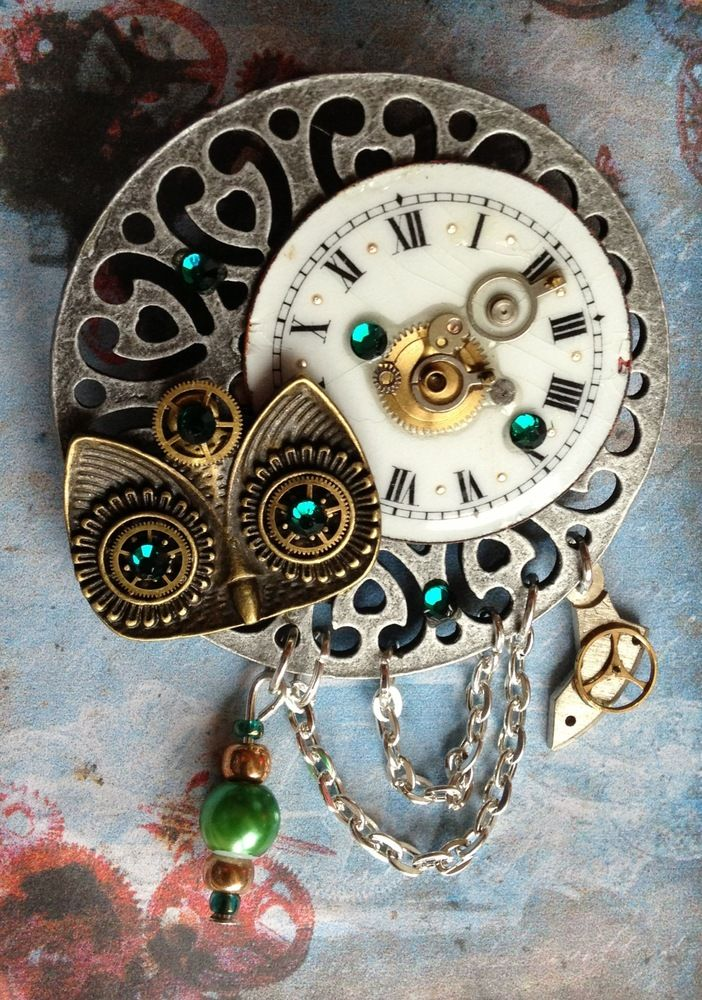 This gorgeous brooch will brighten up any outfit.It's another one of a kind piece from Steampunkalooza.A mixture of silver and bronze tone charms and chain joined with a vintage ceramic watch face and pocket watch cogs and gears make this a stand out piece. Finished off with green crystals and beads to add that extra bit of sparkle. Stunning!