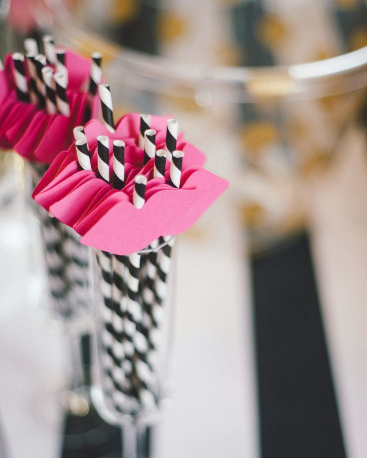 Elevate your bridal shower cocktail with cute pink straws or stirrers, like these striped straws topped with paper cutouts of hot pink lips made by Bake Me a Party.