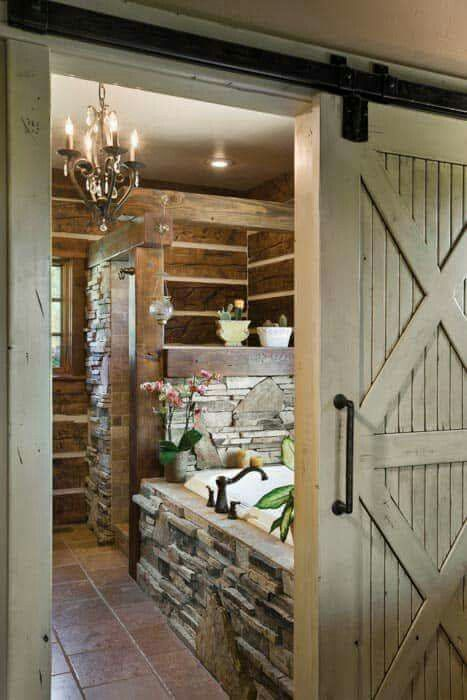 Barn door to a bathroom. Love the rock.