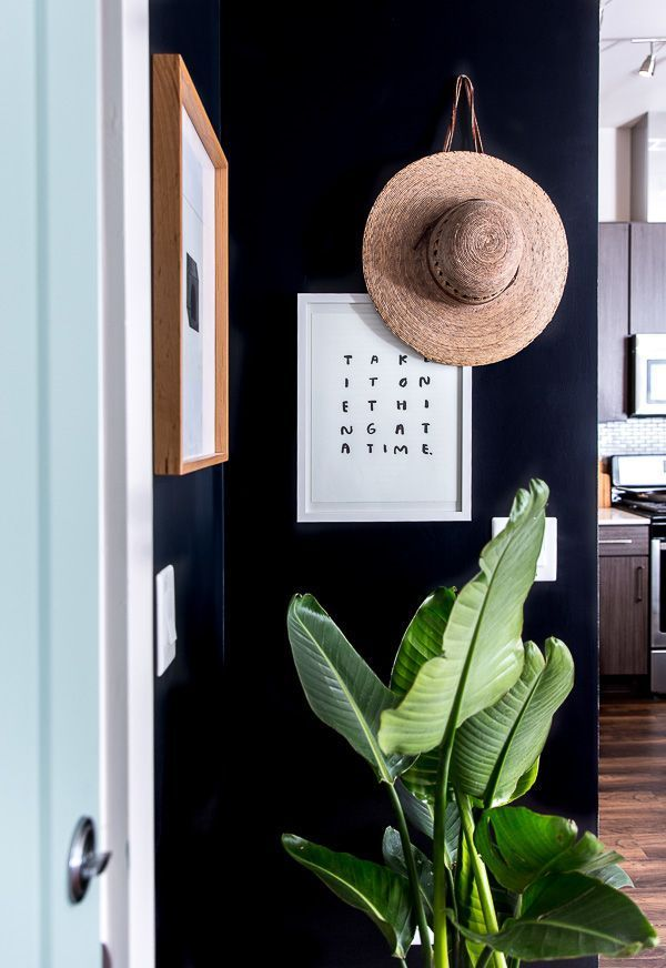 Entrada minimalista com contraste de preto, flores e quadro branco