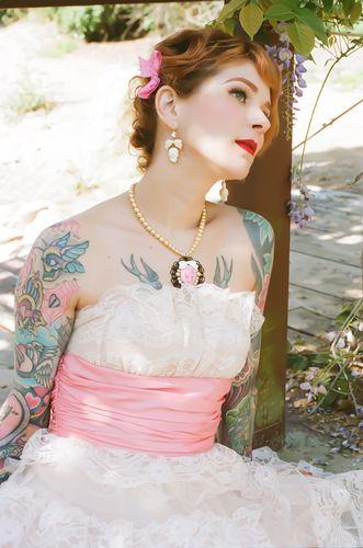 Faixa rosa do vestido combinando com o tom da tatuagem da noiva.