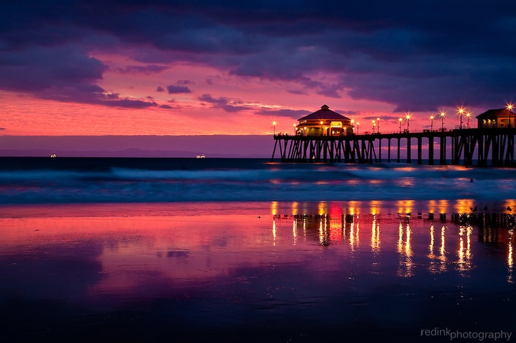 Huntington Beach Pier light up and decorated for the holidays. The pier and pink/blue sunset sky are reflected in the pacific ocean water. Long exposure blurs the ocean. A lone surfer can be seen on the right.