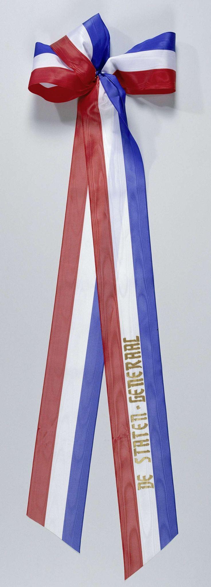 Anonymous | Lint 'De Staten Generaal', Anonymous, 2000 | Twee linten met drie horizontale banen rood, wit en blauw, gelegd op 4 mei 2000 bij het Nationaal Monument op de Dam. Op het bovenste lint in de witte baan een opschrift in goud, onderste lint blanco. Uiteinden schuin afgeknipt. Aan een zijde samengebonden met ijzerdraad, deze is gebogen t.b.v. bevestiging aan krans.