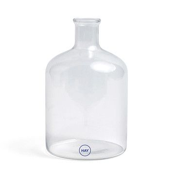 Turkish Cylinder Glass Bottle : The Turkish Cylinder Glass Bottle by Hay is a versatile glass object that impresses with its large, yet simple design. With its bulbous body and narrow opening, the cylinder bottle is reminiscent of a glass jar from a chemistry lab. This association gives the bottle a slight industrial charm and makes it a unique eye-catcher. Can be Used as Jug or Vase, If used as a classic carafe, the cylinder can be filled with juices and other cold drinks; while as a…