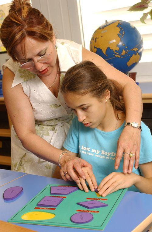 Una maestra trabaja con una alumna con discapacidad visual en el reconocimiento de figuras geométricas.