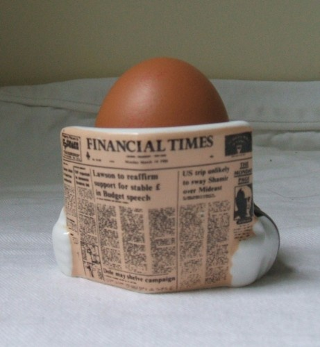 Business Egg is wearing a sharp pinstripe jacket.  Not sure if he has any pants.  Hmmm. Novelty Egg Cup where the egg forms the head of the man reading the  Financial Times dated 14th March 1988