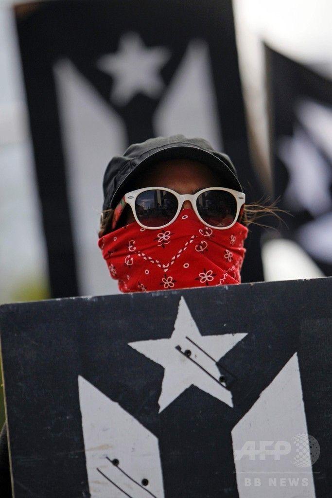 米自治領プエルトリコの首都サンフアン San Juan で、米国の51番目の州への昇格案の是非を問う住民投票に抗議してデモ行進する人(2017年6月11日撮影)。(c)AFP/Ricardo ARDUENGO ▼12Jun2017AFP|米領プエルトリコ住民投票、「51番目の州」昇格を97%が支持 http://www.afpbb.com/articles/-/3131665