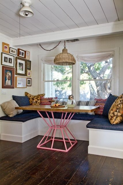 An upholstered bench with assorted accent pillows creates an inviting dining area. Pair with a modern geometric table for a chic look with a pop of color!