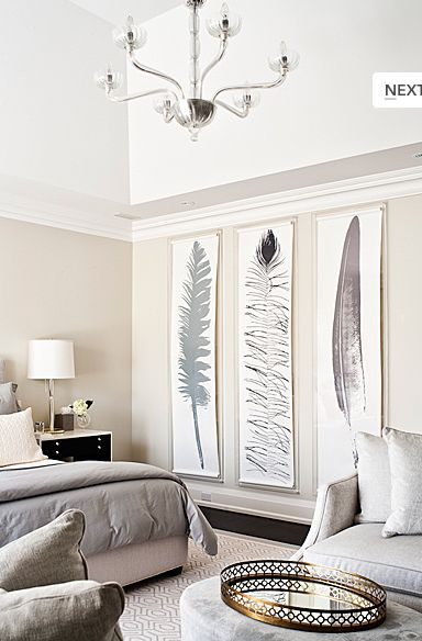 Gray Feathers Bedroom with dark floors, gray walls, dramatic large feather artwork, gray bedding, gray chairs and dark nightstands - by Jennifer Worts Design via Decorpad