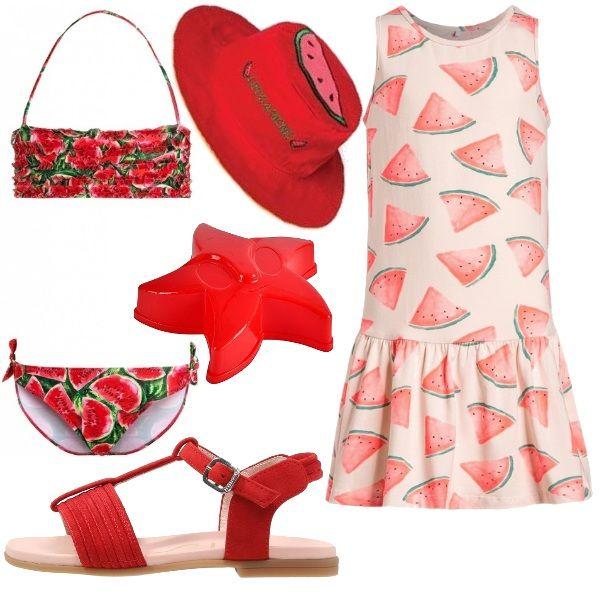 Outfit da spiaggia composto da costumino due pezzi e abito con stampa fette di cocomero, sandali rossi, cappellino con protezione raggi UV rosso e formine per giocare.