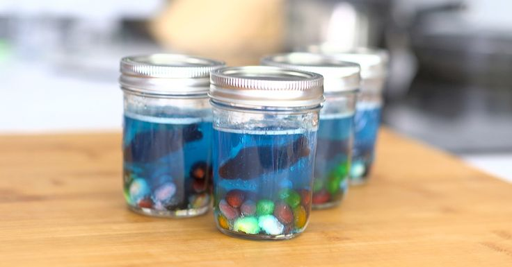 Sprinkle 4 packets gelatin in a large bowl and whisk in boiling soda. Whisk for 5 minutes, or until gelatin is completely dissolved. Pour in remaining 2 cups soda, then add in desired amount of blue food coloring. Stir until fully incorporated and desired color is achieved. Place a small handful of jelly beans into 4 mason jars or clear bowls. This will be your rocky ocean bottom. Divide jello mixture into mason jars. Optional: strain mixture into jars to reduce air bubbles. Place mason…