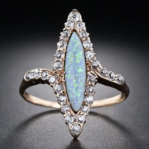 Un anillo antiguo dulce y delgado que destaca una brillante, multi-cromático, ópalo marquesa situado en una ligera diagonal y adornado con pequeños diamantes centelleantes viejas minas de corte. Un anillo victoriana única y maravillosa en deslumbrante de oro rosa.
