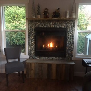 We were trying to decide how to face our fireplace so first went in the hearth, we didn't like the wood the guy used so I put recycled fence boards on front and top of hearth, then we found a live edge mantle for the top and then it all fell into place. Nothing looked right around the fireplace so I went to our beach and picked up all the beach rocks and one by one placed them on and we grouted and we love it.