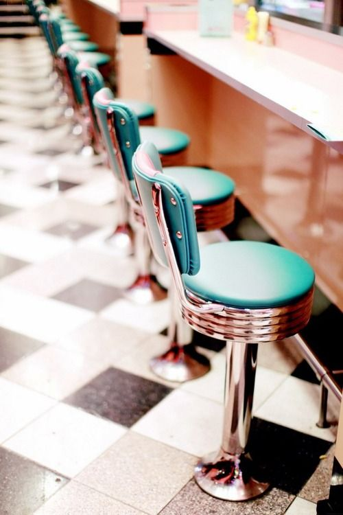 Classic vintage diner stools on top of black and white tile are calling a structured dress fitted on a 20's style woman sipping a thick milkshake.