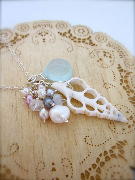 "A beautiful large white sea shell slice is topped with a cluster of opaque white faceted moonstone and creamy white, peacock purple, mauve, bright pink, and silver pearls. It rests beside a stunning, sparkly seafoam blue faceted, heart chalcedony briolette.  This pendant hangs slightly over 1 1/2"" long.  It hangs on a long, dainty sterling silver flat cable chain and closes with a sterling silver handmade clasp and tiny white pearl."