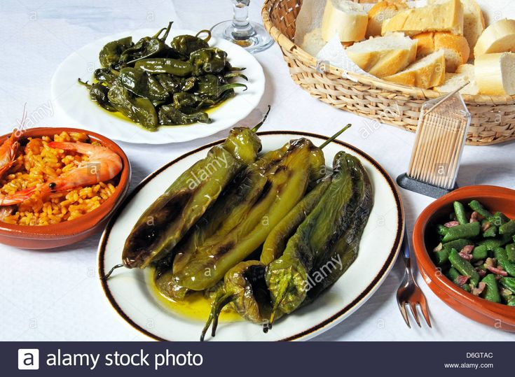 Tapas of Padron peppers, deep fried pointed peppers, seafood and pork paella, green beans with bacon. Stock Photo