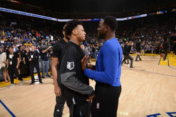 Brandon Rush of the Minnesota Timberwolves talks with Draymond Green of the Golden State Warriors before a game on April 4 2017 at ORACLE Arena in...