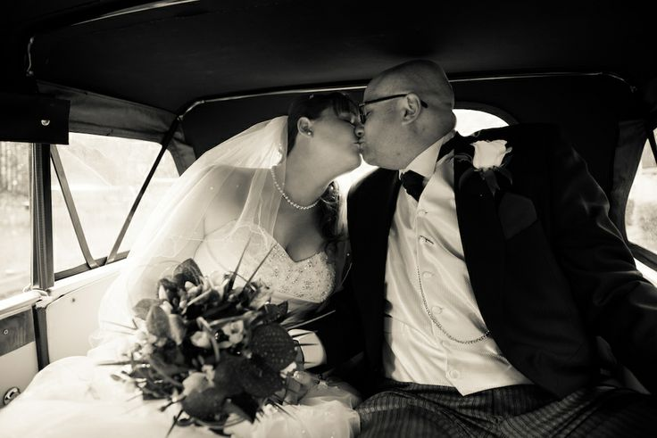 newly weds kissing in the bentley