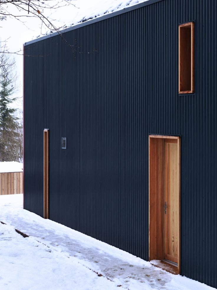 """Private House in Vallée de Joux: location: Yverdon-les-Bains, Vaud, Switzerland; architect: Ralph Germann architectes; year: 2011; descrition: standing on a plot of 800 square meters, a few steps from the Lake Joux's shores, an anthracite metallic shell shields the interior life of this house from the famous harsh climate. Built with local and environmentally friendly materials (""""Minergie"""" Label) that envelope contains a sleek and minimalist interior."""